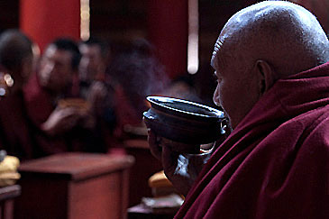 Senior monk eating after prayer session